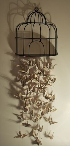 Origami cranes off of a wire house cage. The cranes alone would be cute over a crib.