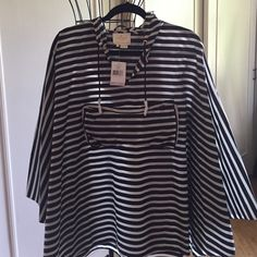 KATE SPADE BLACK/WHITE RAIN PONCHO Black and white rain poncho with a hood.  It can be folded into the front pocket for travel.  Really new up to date styling. kate spade Jackets & Coats Capes