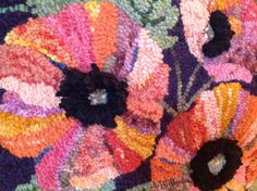 Close up of poppy pillow hooked by Toni Jette