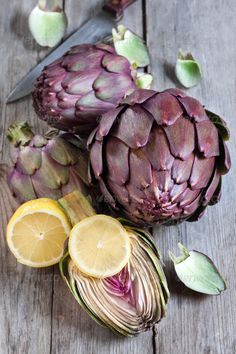 Raw artichokes ...  Artichoke, backgrounds, brown, color, cooking, crop, dietary, eating, food, french, freshness, green, group, healthy, heap, heart, horizontal, ingredient, italian, life, no, objects, organic, purple, raw, season, section, shot, still, table, thorn, two, vegetables, vertical, white, wood