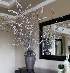 Dramatic centerpeice - hot glue dollar store flower blossoms onto branches.