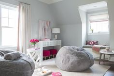 Hot pink and gray teen girl's bedroom features walls painted light gray fitted with a built-in window seat lined with a gray quilted bench cushion and a pink and gray geometric lumbar pillow as well a pink and gray color block throw blanket.