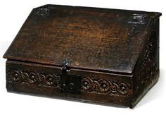 A CHARLES II OAK SLOPE-LID BOX  LATE 17TH CENTURY  With guilloche band, the sides with large rosettes