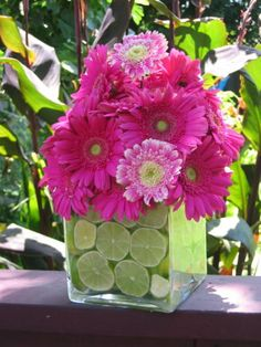 pink and green wedding cakes | Pink Gerber daisies overflow atop a vase filled with green lime slices ...