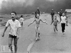 South Vietnamese forces follow after terrified children, including 9-year-old Kim Phuc, center, as they run down Route 1 near Trang Bang after an aerial napalm attack on suspected Viet Cong hiding places on June 8, 1972. A South Vietnamese plane accidentally dropped its flaming napalm on South Vietnamese troops and civilians. The terrified girl had ripped off her burning clothes while fleeing. The children from left to right are: Phan Thanh Tam, younger brother of Kim Phuc, who lost an eye, Phan Thanh Phouc, youngest brother of Kim Phuc, Kim Phuc, and Kim's cousins Ho Van Bon, and Ho Thi Ting. Behind them are soldiers of the Vietnam Army 25th Division