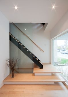 #colizzabruni #modern #hintonburg #infill #home #design #interior #minimalist #ottawa #stair #handrail From the ground floor level of the front unit, stairs rise in front of a floor-to-ceiling window and takes you up to the primary living level raised 1 storey above the street.