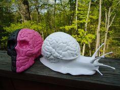 3D printed snail next to skull/brain.
