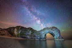 The Milky Way seen behind the natural archway of Durdle Door in Dorset, U.K.