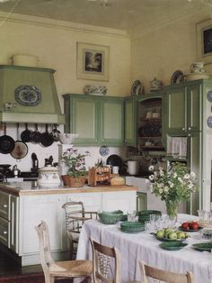 Lots of natural light. Blue Spode. Attached dining space. Green cabinets. (Original source unknown; possibly UK's House & Garden)