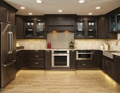 Dark maple wood cabinets in kitchen with full tile backsplash. See more in our kitchen cabinet gallery.