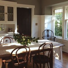 .The dark gray walls personalize an all white kitchen and give it character as do the bentwood and windsor chairs.