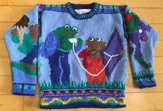 This is a pattern for a handknit sweater for a five or six year old Frog and Toad enthusiast. On the front Frog and Toad are trying to launch their purple kite. On the back the golden snake is emerging from his cave while Frog and Toad run away. On the left sleeve Frog is happy about his many-buttoned jacket. On the right sleeve Toad is carrying two ice cream cones back to Frog. The hem has two patterns, one of snakes against a green and blue background and the other of red and black…