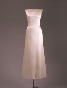 "Ivory Evening Dress Maker: Oleg Cassini (American, b. France, 1913-2006) Date(s) of Materials: 1961 Place Made: United States Medium: Duchesse silk satin Dimensions: 56"" center back Description: An ivory silk evening dress with bateau neck. This plain front gown is floor length and sleeveless. Historical Note: This dress was worn by Jacqueline Kennedy to the White House dinner honoring President and Mrs. Harry S. Truman, Washington, DC, November 1, 1961."
