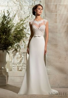Modern and Chic Morilee Wedding Dress. Illusion neckline with lace appliqués and adorable front bow. Sleek Sheath skirt. High Neckline with lace bodice and illusion back. Style 5301.