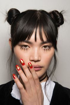 """The look: Pro manicurist Miss Pop created a Hollywood Walk of Fame–inspired nail.""""I added graphic gold stars rising up the nails, boldly standing front and center, and co-starring in corners,"""" she explains.""""It's an element that takes that aspirational glamour of L.A. and makes it DIY.""""  The kit: Acustom mix ofCND VinyluxWeekly Polish in  Banana Clips andElectric Orange, topped with a  layer of Wildfire."""