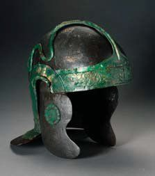 Thorsberg. Roman cavalry helmet, type Nederbieber III. The decoration consists of a band of hair curls across the forehead, which is connected by a narrow band to a plate on the neck guard by way of a plate with a  rosette on the top centre of the helmet. On the neck guard plate there is a wreath and a thunderbolt. From the top centre of this plate two snakes crawl along the sides up to the top of the helmet. Photo: Archäologisches Landesmuseum Schleswig. Inv. nº FS 2500 Rad 400.