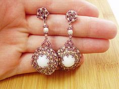 Biela perla obšívaná fialovými a ružovými korálkami.