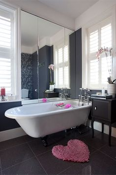 Sometimes a room just needs a bit of TLC to take it from routine to romantic. Here, a stormy-gray bathroom is softened with feminine touches and pops of bright pink for a fresh, eclectic feel. We've sourced some of these sweet accessories from our friends at overstock.com so you can get this look now.