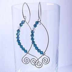 brincos em formato de peixe em fio de prata com cristais azuis