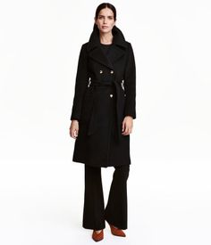Black. Double-breasted coat in a wool blend with lapels, gold-colored buttons and patch pockets at front, detachable tie belt at waist, and vent at back.