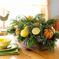 decoração de mesa - centerpiece com laranjas com cravos e muito verde - tudo indica que montado numa caixa de vinho