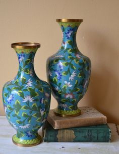 Wonderful piece of Chinoiserie Decor. Pair of vintage Cloisonne Vases in cool toned blues and greens. Ornate wooded stands included.    Size: 10 1/2