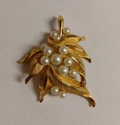Vintage Trifari gold tone and faux pearl brooch. Gold tone leaves and 13 faux pearls. Used, great condition. Approximately 2 5/16 x 2 3/16. Item will ship 1-3 business days after receipt of payment. Thank you for looking. *I ship USPS **package fee applies to most orders ***PLEASE