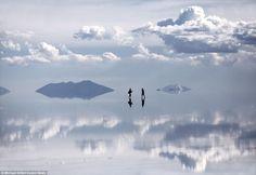 美国摄影师Michael Kittell与妻子Taylor环球旅行来到了玻利维亚的乌尤尼盐沼是世上最大的盐沼,这是一片地表有几厘米深的水覆盖的广阔平原,没有风,天空和云彩的景象完美的倒映在地面之上。