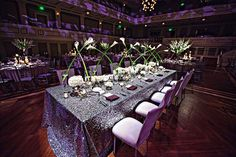 Long-stemmed calla lilies criss-crossing along the table really pop against glittery table linens.