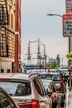 Just love this view of Old Ironsides from the North End in Boston. I was casually walking from the Haymarket to the North End, when I saw this view of the USS Constitution down a side street in the North End. The view was so spectacular, that I abruptly stopped and snapped this photo. I put a slight HDR look into the photo to bring out the reflections and the detail in the street and on the frigate.