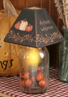 """Primitive Autumn Welcome Pumpkin Lamp - This is a new item for fall. It is an electric light inside a glass jar with a wooden shade that sits on top. It is painted black with bittersweet and pumpkins and says Autumn Welcome. It measures 11"""" tall."""