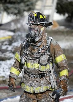 A firefighter is covered with ice as firefighters battle a house fire Monday morning.