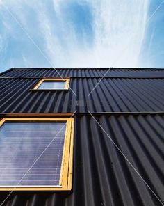 living4media - house facade with black corrugated metal cladding and light wooden windows