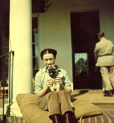 Tense: Wallis, more used to life in the elegant salons of Palm Beach, seeks solace with her pet pug during a trip to the Florida retreat