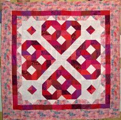 """""""This quilt was constructed with one simple block repeated over and over in different colorways. It is assembled in rows rather than as bloc...  I like the hearts"""