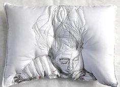 Des dormeurs brodés s'incrustent dans l'oreiller