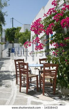 classic greek taverna furniture restaurant cafe on the stone painted street greece islands with flowers - stock photo