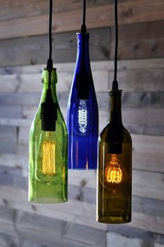 is a light chandelier made from three different recycled wine bottles - cobalt blue, green and olive colored glass. There is a variety of Old Wine Bottles, Recycled Wine Bottles, Wine Bottle Art, Lighted Wine Bottles, Diy Bottle, Bottle Lights, Wine Bottle Crafts, Wine Bottle Lighting, Empty Bottles