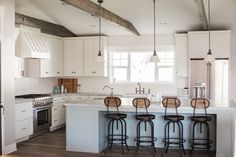 Custom kitchen space with white shaker style cabinetry, large oversized island, and vaulted ceiling - by Rafterhouse.