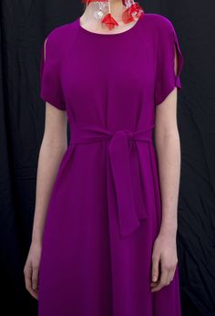 A simple, joyful line makes this short-sleeved dress come alive. The A-line cut looks at its best with the same fabric belt tightened at waist with a simple knot. For added playfulness, the shoulders are cut out. Short Sleeves, Short Sleeve Dresses, Dresses With Sleeves, A Line Cut, Sleeved Dress, Joyful, Magenta, Knot, How To Make