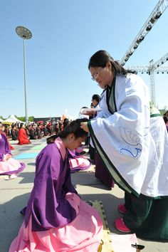 A girl receives a hairpin to symbolize her journey from child to adult. This coming of age ceremony was sponsored by CYRTV and was held during the 2nd Annual Shanxi Radio and TV Carnival.