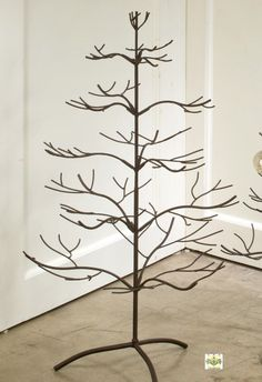 """This brown natural tree features one of our most popular  """"root"""" designs. Comes with a beautiful mahogany brown metal  finish and stands 36"""" high x 20.75"""" wide and 19.75"""" deep. Base measures approximately 13.25"""" wide. Arms on this tree are stationary and do  not move. Simple assembly is required. This is a  great tree for hanging ornaments, family pictures or  hanging collectible that you'd like to showcase! Holds 50 ornaments up to 3"""" in diameter.  Additional ship fees may apply on orders…"""
