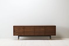 Fresh out of the shop is our latestcredenza, with 4 doorsmade from one  slab of solid walnut. The brass pulls were custom designed by the guys  across the hall at Clear Irons studio. The base is powder coated steel with  solid brass, adjustable feet.