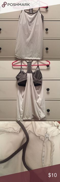 Fabletics built in bra tank Fabletics built in bra tank. I do not know the size since I cut it off but it is most likely a medium. White tank. Bra is grey. Bottom is a tie to tighten the bottom if you please. There are cut outs in the bra of you wish to put padding in the bra. Fabletics Tops