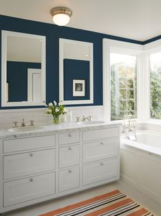 This bath's walls, in Kelly-Moore Peacock Blue KMA29, feel sumptuous paired with luxe white finishes and gleaming hardware.