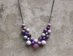 A cocktail of lilac and purple with a little grey and silver in this Valerie Berry bib necklace. Dyed wood makes her beautifully light to wear, I added a Czech glass bead and matt acrylic faux rock for a little sparkle. Valerie Berry is 21.5 inches (55cm) around, including the beads, hung on a polished cotton cord. Convo or let me know in notes to seller if you would like a different length. Largest beads are 15mm (5/8).  She comes in a cute gauze bag, already gift wrapped. Valerie Berry…