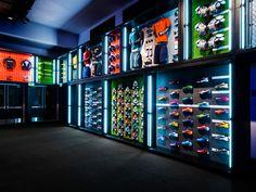 Carlos: interior de tienda de futbol, con grandes luminosos de colores, es una tienda oscura y brillante