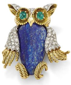 A lapis lazuli, diamond and emerald owl pin, by Van Cleef & Arpels. Modelled as an owl, the central bevelled lapis lazuli body accented with pavé-set diamond wings, head and ears, to oval mixed-cut emerald eyes, length 4.3 cm, c. 1960, signed 'V.C.A'. Via Phillips.