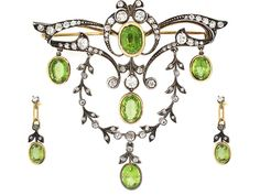 Indulge in elegance with this voluptuous Victorian Peridot and Diamond set. A magnificent melding of glittering old mine cut diamonds and verdant peridot creates a sublime swagged vine style which will make you feel like royalty. This sumptuous creation features a diamond brooch with peridot drops which has a detachable peridot studded chain for convertible style and dazzling peridot drop earrings.