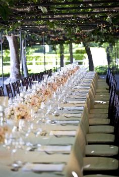 A gorgeous banquet table filled with pastel roses and silver, under a canopy of vines